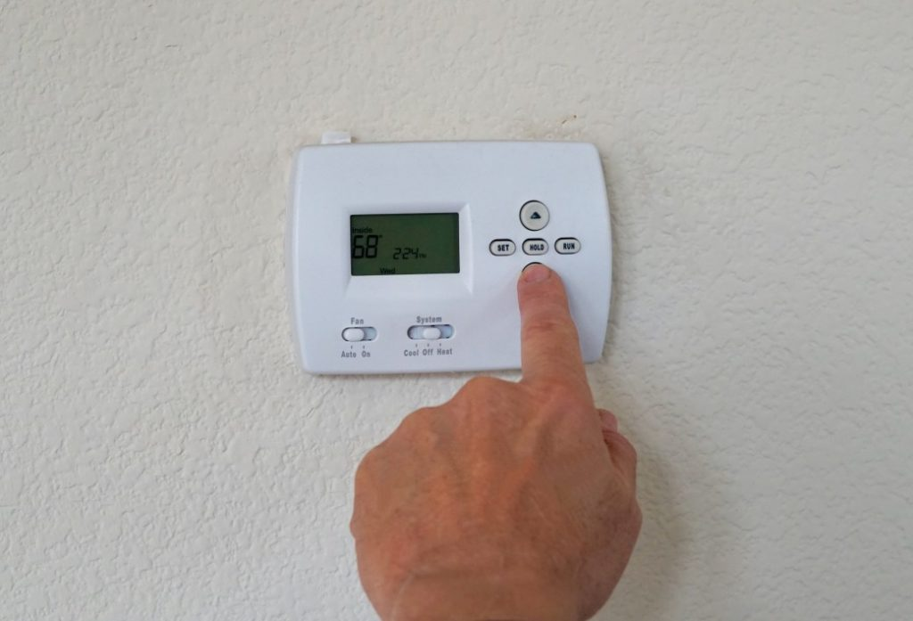 thermostat being adjusted