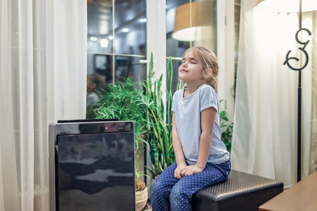 little girl sitting next to an AC