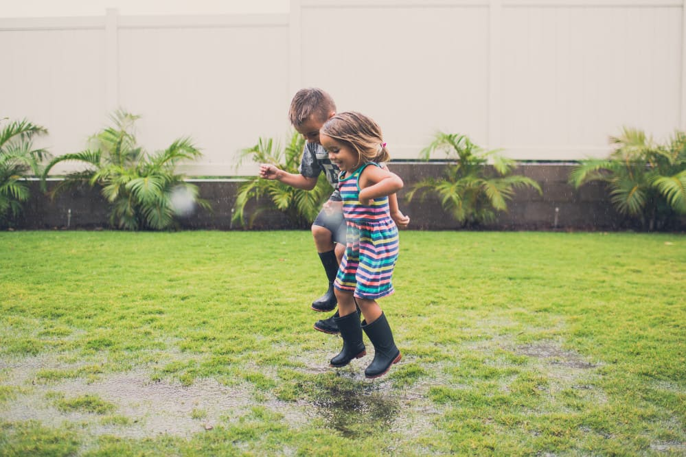 kids jumping in the rain