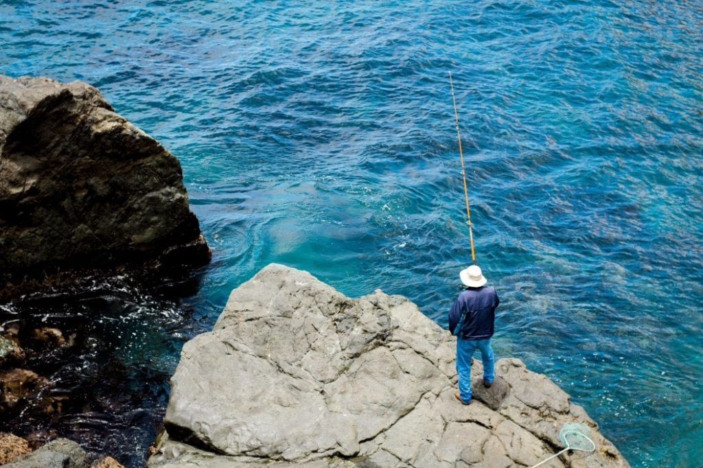 man fishing off a cliff